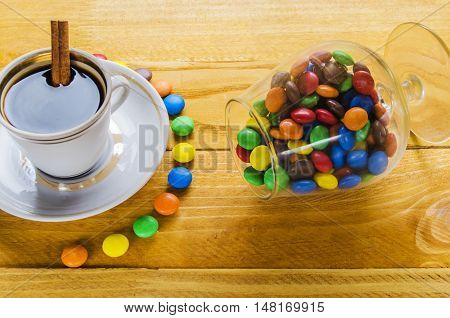 cup of hot coffee with grains and candies