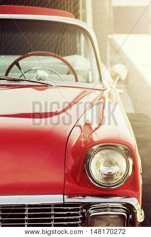 Up close shot of red retro convertible car gleaming in the sunshine
