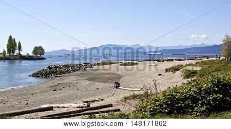 Vancouver, BC - April 20, 2015 - Beautiful, idyllic shot of Sunset Beach Park with some people sitting on a long log in the distance. Shot from the Burrard Bridge with English Bay in the background which is full of boats, sailboats and cargo ships on a go
