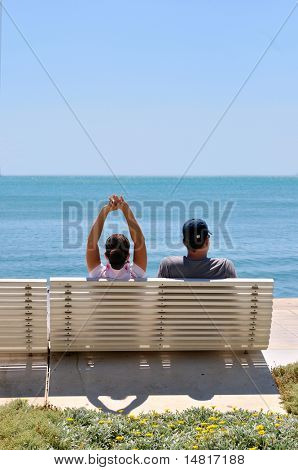 Happy young couple sitting on the beach relaxing