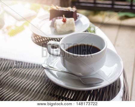 Hot black coffee in white ceramic cup on wooden table.