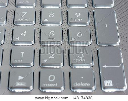 Number keys on silver keyboard of laptop, close up, horizontal image. Shallow DOF