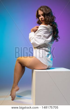 Erotica. Curvy girl posing in shirt while sitting on cube