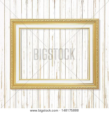 Antique gold frame on white wooden wall. Empty picture frame on white wooden wall.