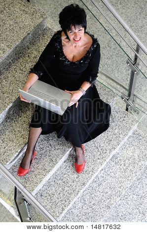 senior business woman work on laptop at modern staircase