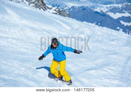 Active young man riding a snowboard down the slope
