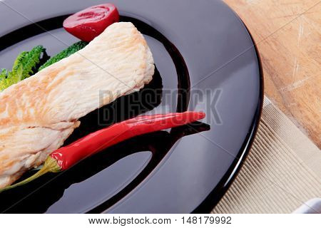 fresh roast turkey meat steak fillet with red hot pepper and green lettuce salad kale on black plate over wooden table with knife and fork