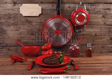 red theme lunch fresh grilled bbq roast beef steak red plate green chili tomato soup sauce paprika small jug glass ground pepper american peppercorn modern cutlery served wooden table empty nameplate