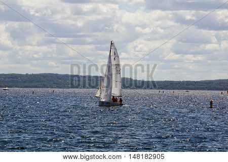HARBOR SPRINGS, MICHIGAN / UNITED STATES - AUGUST 1, 2016: A sailboat sails on Little Traverse Bay near Harbor Springs.