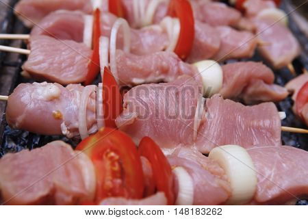 fresh raw turkey pork red meat fillet shish kebab on wooden skewers over vintage kind brazier full with ready charcoal