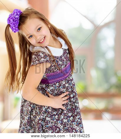 Happy little girl with a big purple bow on her head , and fancy dress. The girl bent her head to see her long beautiful hair.In the room with large, bright Windows.