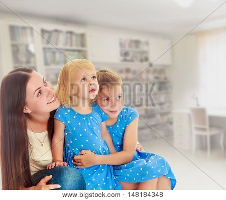 The concept of family happiness and mutual understanding between parents and children.Beautiful young mother with her two daughters. All look up.