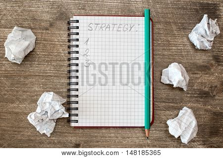 Notebook for strategy and crumpled paper on the wooden desk