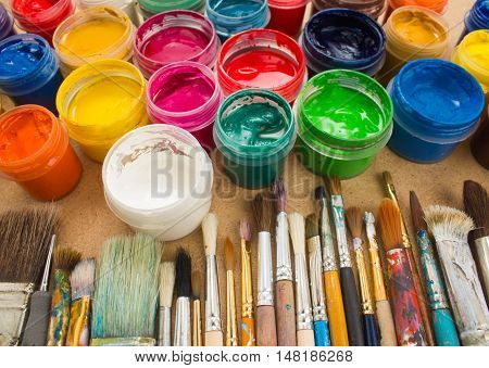 Colorful paint, brushes, palette on wood background