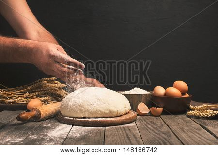 Men hands sprinkle a dough with flour close up