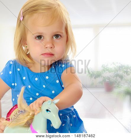 Cute little blonde girl playing with a toy horse. Girl wearing a blue dress with polka dots.Against the background of a child's room . The concept of the holiday and the New year.