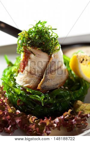 Japanese Cuisine - Chuka Seaweed Salad and Eel with Nuts Sauce. Served with Lemon and Sesame