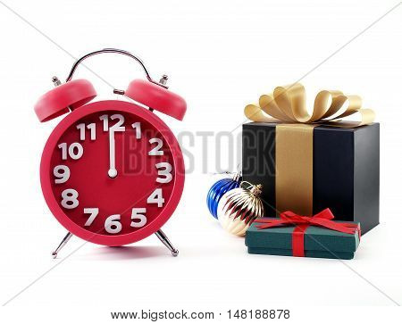 minutes before new year on red alarm clock and two gift boxes with colorful Christmas balls isolated on white background, concept about countdown to New Year