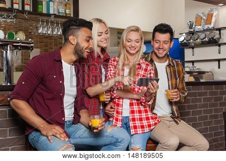 People Friends Using Cell Smart Phone, Drinking Orange Juice Talking Laughing Sitting At Bar Counter, Mix Race Man And Woman Happy Smile Communication