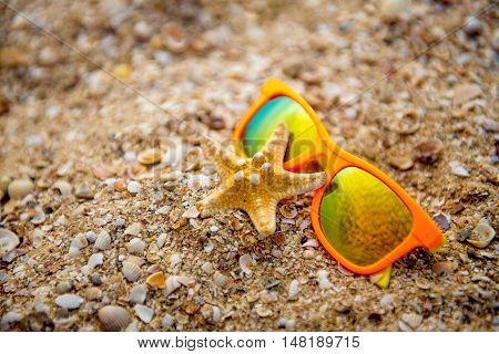 sun glasses and starfish on white sandy beach. Summer vacation concept