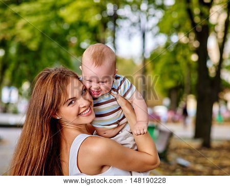 Portrait of happy loving mother and her baby outdoors in park. Autumn park outdoor.