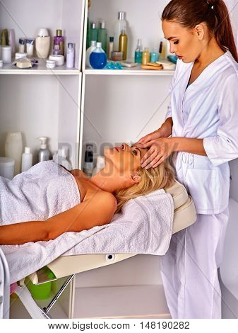 Woman middle-aged take face and neck massage in spa salon. Anti-aging rejuvenation spa.