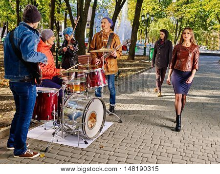 Music street performers with girl violinist on autumn outdoor. Passers by walk past musicians