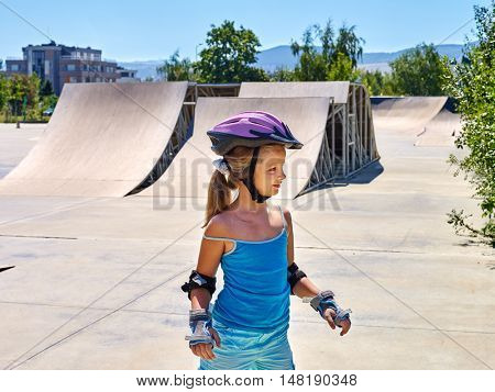 Sport girl riding on roller skates in skatepark. Summer sport park.