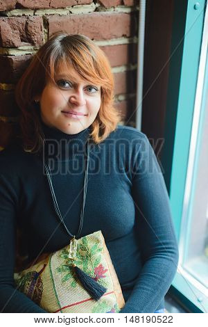 redhaired young woman in cafe near the window