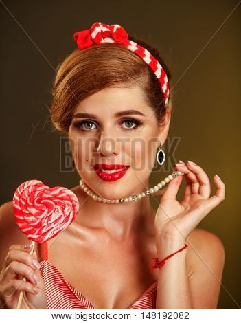 Portrait of girl in pin-up style keep big striped lollipops. Pin-up retro female style. Girl pin-up style wearing bead.