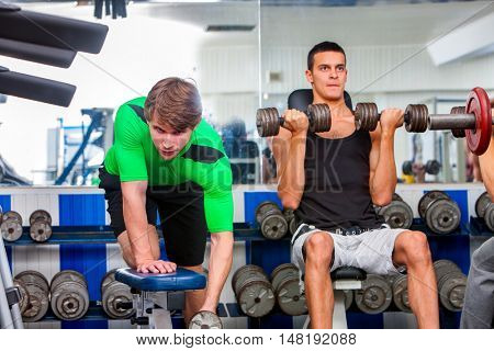 Group of men working on simulator with heavy dumbbells his body at gym. Men's sports training in sport gym.