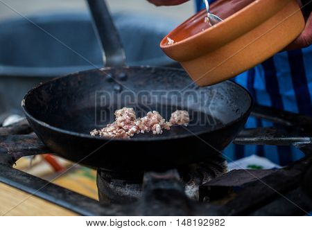 cooking, asian kitchen, sale and food concept - cook putting forcemeat on frying pan at street market on gas stove at asian street market