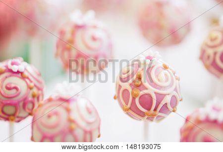 food, sweets, junk-food, confectionery and eating concept - close up of cake pops or lollipops