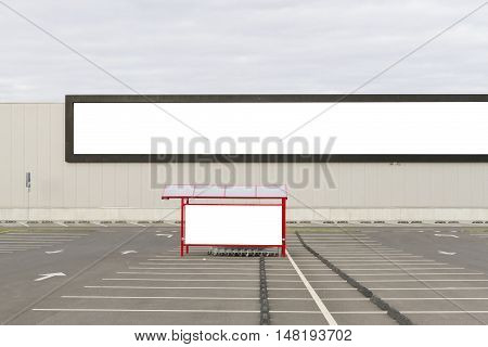 Mock up. Big horizontal store billboard and shoping trolley bay in a parking lot.