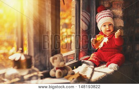 happy baby boy in a red suit about autumn window