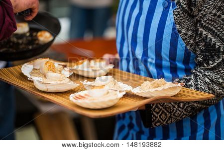 food, cooking and eating concept - close up of waiter holding tray with scallop snacks served with garnish on seashells