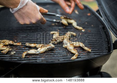 cooking, asian kitchen, sale and food concept - close up of cook frying frog meat on grill at street market