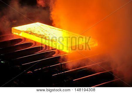 Hot steel plate on conveyor, close up