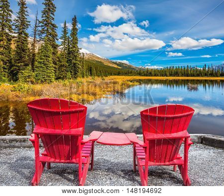 Two red comfortable deck chairs on the lake. The beautiful nature in northern Rocky Mountains of Canada