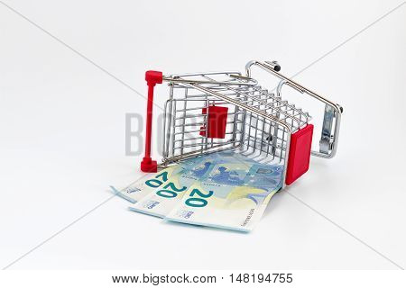Small shopping cart with euros banknotes. Conceptual representation of wrong choice error but also economic weight.