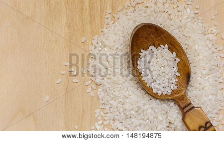 A pinch of rice and a wooden spoon on the board