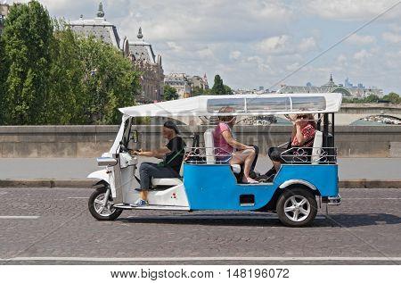 PARIS, FRANCE-AUGUST 09, 2016: tourists on a city tour in a tuk tuk in paris