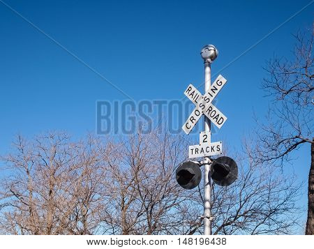 Railroad crossing sign against blue sky and tree background with space for your text.