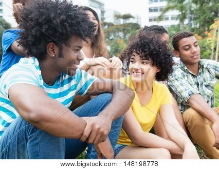 African guy speaking with girlfriend with multiethnic group outdoor in a park in the summer