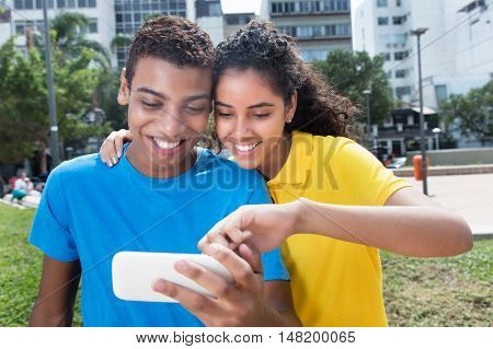 Latin american couple with colorful shirts showing photos outdoor in a city in south america