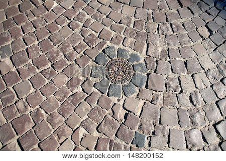 Manhole with drainage sewerage surrounded cobblestones background texture