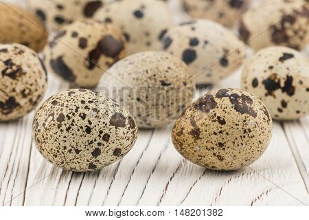 Quail eggs on old white wooden table. Selective focus.