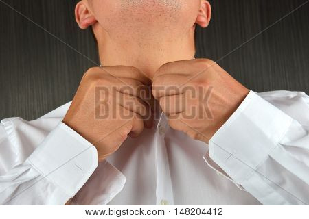 Young Man Buttoning His White Shirt At The Neck. He Is Dressing In The Morning. Clothes Detail. Ligh