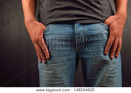 Close Up Of The Hands With Big Fingers In Pockets Of His Blue Jeans Of A Young Man Wearing Grey Blan