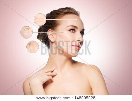 beauty, people and aging concept - beautiful young woman touching her face over beige background